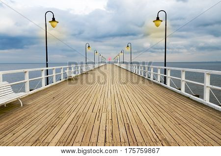 Symmetrical woden pier with lanterns on a sea with dramatic sky.