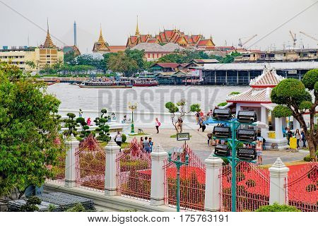 Bangkok, Thailand - January 9, 2016: The Grand Palace from across the Chao Phraya River view from the biggest stupa of Temple of Dawn, Wat Arun, Bangkok, Thailand. Ancient Thai classical architecture