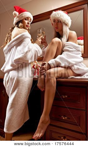 Portrait of two sexy girls in Santa hats with the glasses of champagne waiting for New Year
