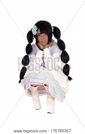 A beautiful African American woman crouching in long white boots and a blue dress with long black hair isolated for white background.