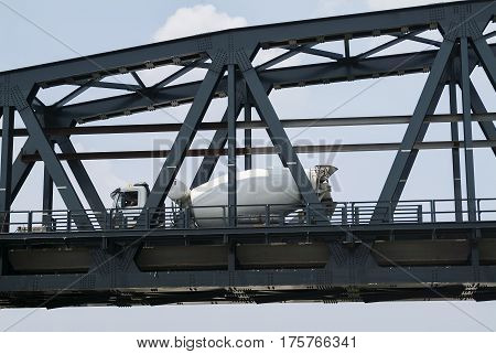 White Cement mixer in transit on the metal bridge