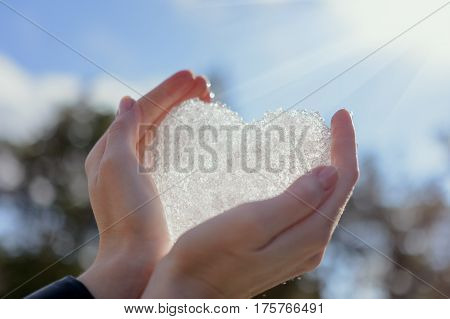 Human hands heart against snow background St.Valentine's Day romantic concept
