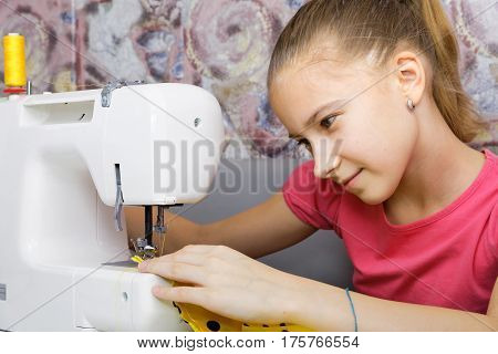 The girl sews the fabric on an electric sewing machine