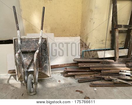 Construction metal wheelbarrow cart standing upside at the left corner and boarding wood on the construction site abandon building wall sand truck cart