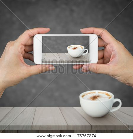Woman hand holding and using mobilecell phonesmart phone with isolated screen and redolent cappuccino coffee on wooden floor with blurred image of abstract background.