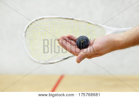 squash racket and ball in men's hand. Racquetball equipment. Photo with selective focus. Player prepares to serve a squash ball. Closeup of male hand serving ball