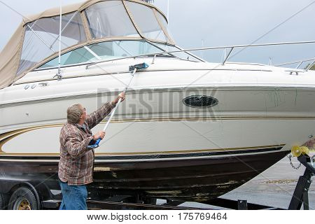 Caucasian man using long brush to clean power boat