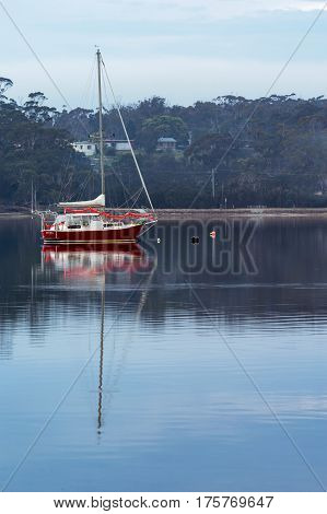 Boat rests in still water in St Helens on the East Coast of Tasmania, Australia.