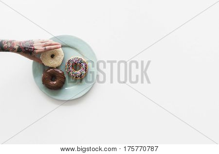 People Hands Reach for Doughnuts on the Plate