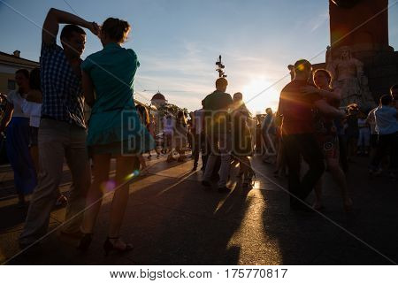 ST. PETERBURG, RUSSIA - CIRCA JULY, 2016: People dance to Latin music on the Spit of Vasilyevsky Island. Spit of Vasilyevsky Island is a popular place with locals and tourists. Focus in background.