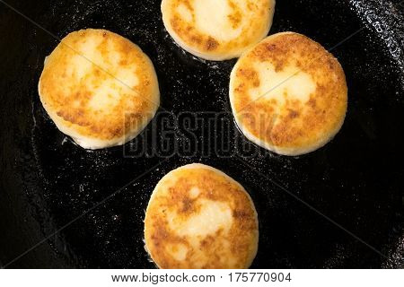 Beautiful pancakes made of cheese in a black frying pan. Cheesecakes. Pancakes curd. Pancakes fritters, a traditional dish of Russia and Ukraine.