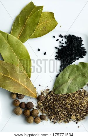 Dried bay laurel leaves and peppercorns isolated on a white background, close up view from above