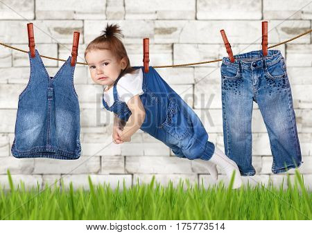 failed housework concept Funny child hanging on clothesline