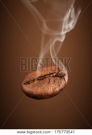 falling coffee bean with smoke on brown background