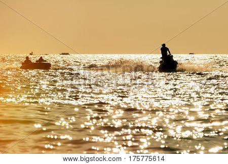 Silhouette of man on jet ski in the sea at high speed skating people on a large Inflatable ring at sunset