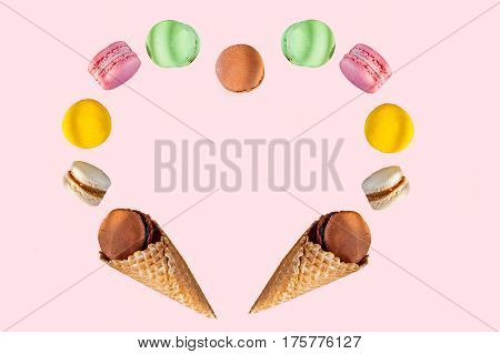 Multicolored Cake Macaron Or Macaroons And Waffle Cones In The Form Of A Heart Frame On The Pink Bac
