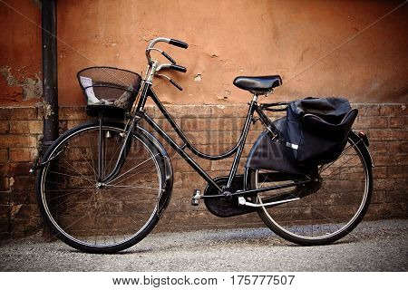 Old retro bicycle with basket against a grungy wall in Ravenna, Italy