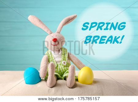 Spring break concept. Colorful Easter eggs and toy bunny on sand