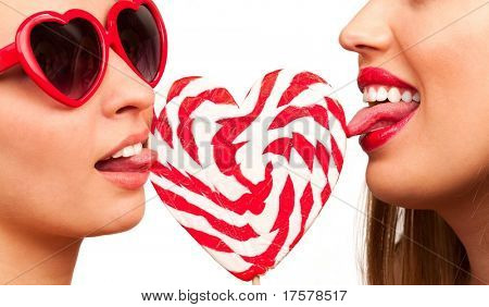 Closeup of pair young sexy women with heart shaped lollipop and sunglasses