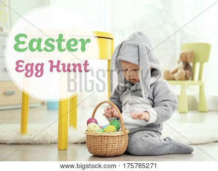 Easter hunt concept. Baby in bunny costume with eggs at home