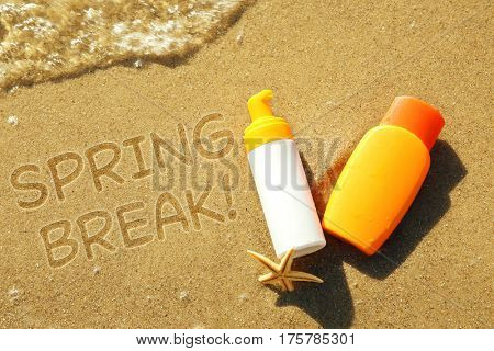 Spring break concept. Lotion bottles with starfish on sea shore