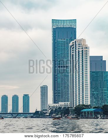 View of the bank of the Chao Phraya River with skyscrapers bridge and several boats on the river. Downtown of Bangkok Thailand.