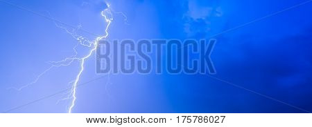 Thunderstorms thunder lightning night sky clouds overcast summer rain background panorama and with space for text.