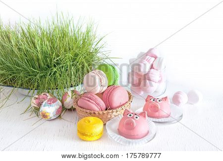 delicate Easter sweet song of the macaroon, eggs, marshmallow, sweet pies, pigs in pastel colours on a background of green young grass