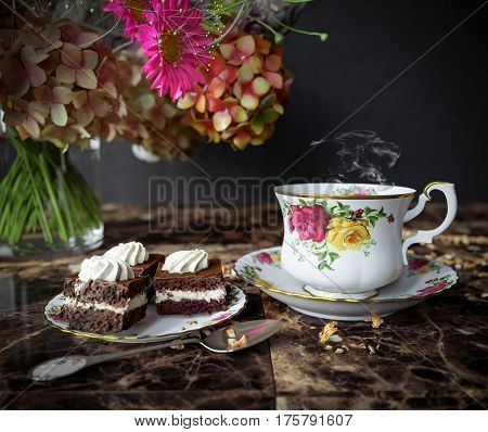 Closeup of cup of tea with cake and flowers bouquet on the wood table close up photo