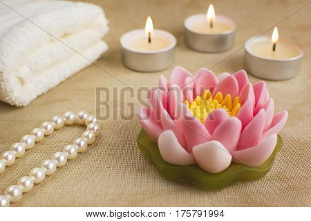 Beautiful handmade soap shaped like lotus flower. Burning candles string of pearls and towel on the background. Spa concept.