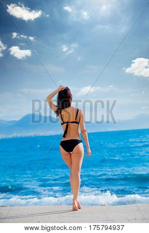 beautiful young woman standing in front of wonderful sea background in Greece