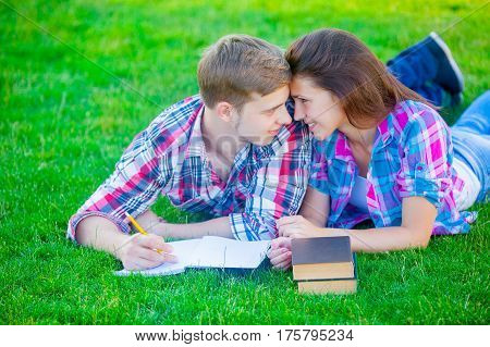 beautiful cute couple lying on the field and studing with books