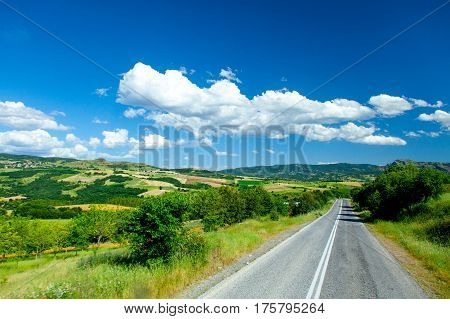 photo of the beautiful asphalt road in front of wonderful huge field background in Greece