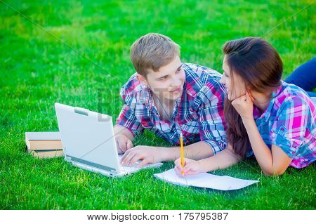 beautiful cute couple lying on the field and studing with books and laptop