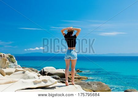Beautiful Young Woman Standing On The Wonderful Stone Coast In Greece