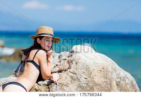 Beautiful Young Woman Standing Near Big Stone On The Beach In Greece
