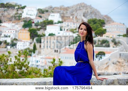 Photo Of Beautiful Young Woman Sitting On The Stairs On The Town Background In Greece