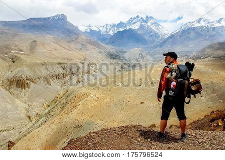 A traveler with a backpack in the Himalayan mountains looks at the gorge. Nepal. Kingdom of Upper Mustang.