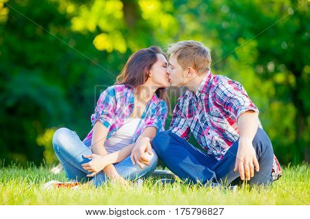 Beautiful Cute Couple Sitting On The Field And Kissing On The Trees Background