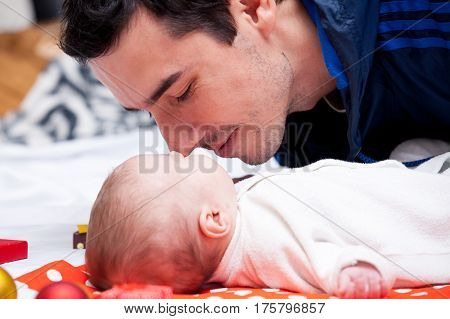 photo of father kissing his sleeping baby near gifts and baubles lying on white blanket