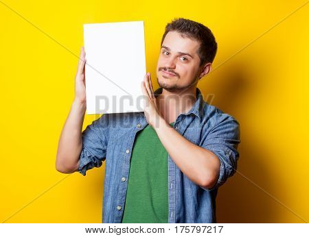 handsome young man holding white poster on the wonderful blue background