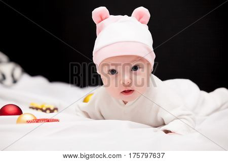 Beautiful Cute Baby In Hat Near Gifts And Bauble Lying On The White Blanket