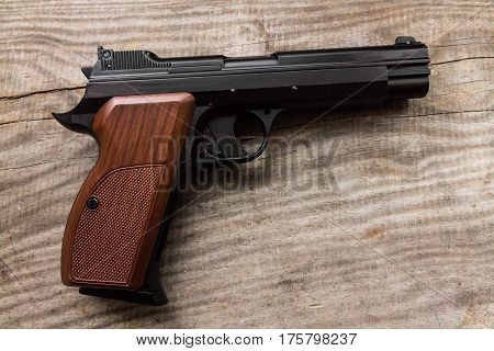 Pistol on a wood background. Handle left.