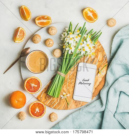 Cup of morning coffee, cookies, red oranges, bucket of spring flowers and mobile phone with text Good morning on board over light grey marble background, top view. Morning greeting card concept