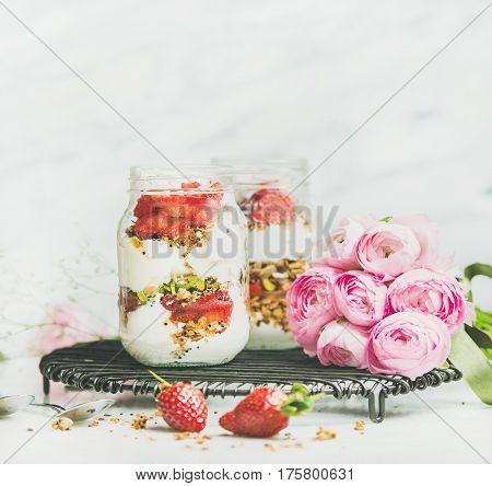 Healthy spring breakfast. Greek yogurt, granola, strawberry breakfast in glass jars, pink raninkulus flowers, marble background, selective focus, copy space. Clean eating, detox, diet food concept
