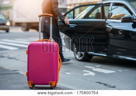 People taking taxi from an airport and loading carry-on luggage bag to the car. Luggage on the city street. Travel concept.