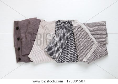 Stack of women's knit cardigans and sweaters in neutral colors. Top View.