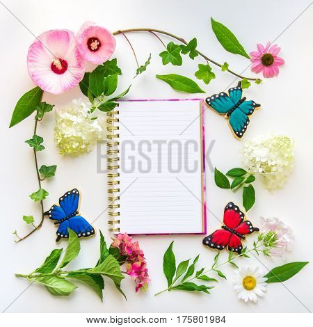 Colorful flowers and homemade butterfly cookies floral composition with notebook on light background. Top view flat lay.