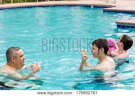 Family with cute baby girl faving fun in outdoor swimming pool on hot summer day.