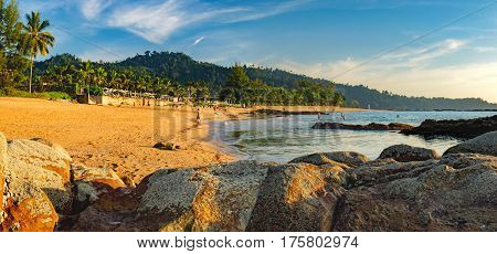 Beautiful seascape with sea and rock in Nang Thong Beach, Khao Lak, Thailand. View of bright blue sea with protruding stones in the foreground and crowded beach with bathing and walking people